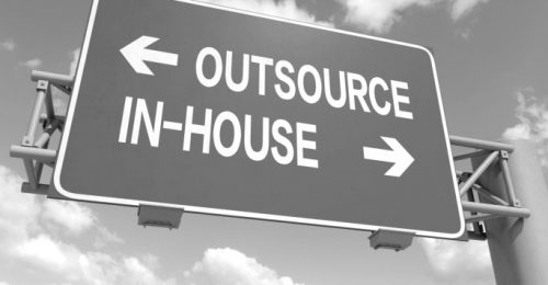 road sign directing to outsource or in-house