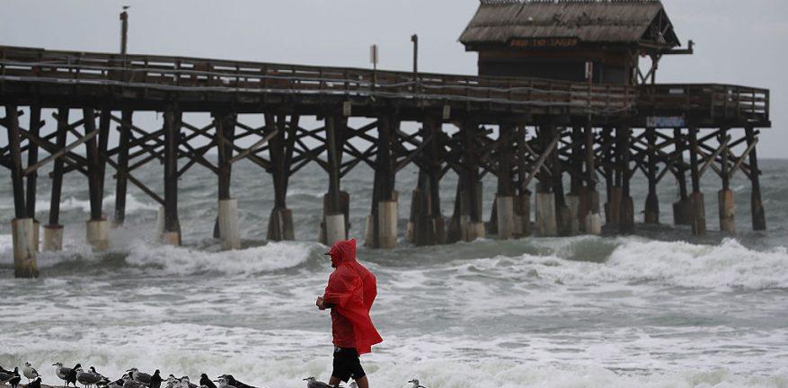 A man walks near the Cocoa Beach Pier as Hurricane Matthew approaches October 6 2016
