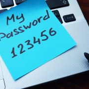 Someone's bad password posted on a sticky note on a laptop.