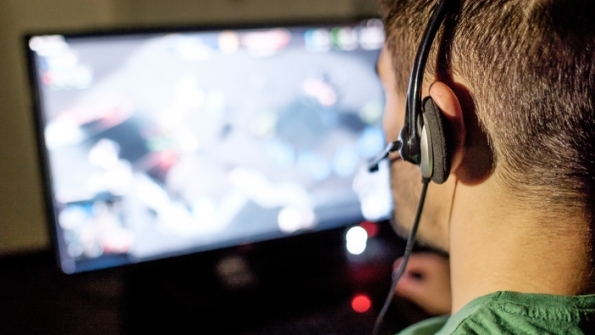 Man with headset watching computer monitor
