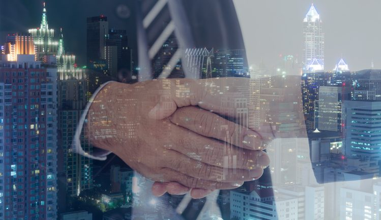 Business handshake with cityscape by Thinkstock