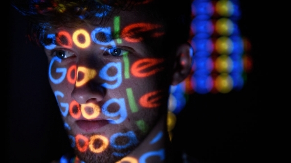 Google logos projected on man's face
