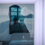 Man taking picture reflected in window