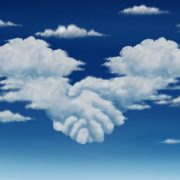 Two cloud-shaped hands shaking among other clouds in the sky.