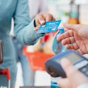 Woman handing over credit card to be processed on POS device