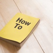 "The words ""how to"" on a book sitting on a table."