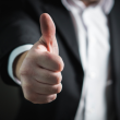 Man's arm gesturing with a thumbs up hand signal