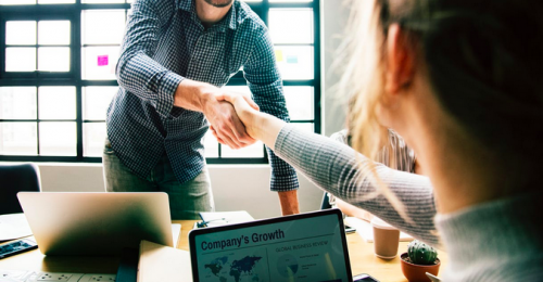 Businesspeople shaking hands over a conference table