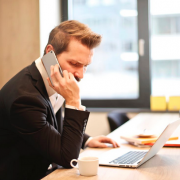 Businessperson on phone with computer and coffee cup