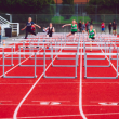 Track with runners jumping hurdles