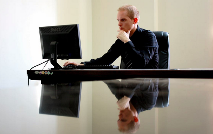 Man sitting at table in front of computer monitor