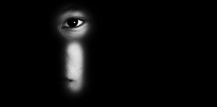 Person peering through keyhole