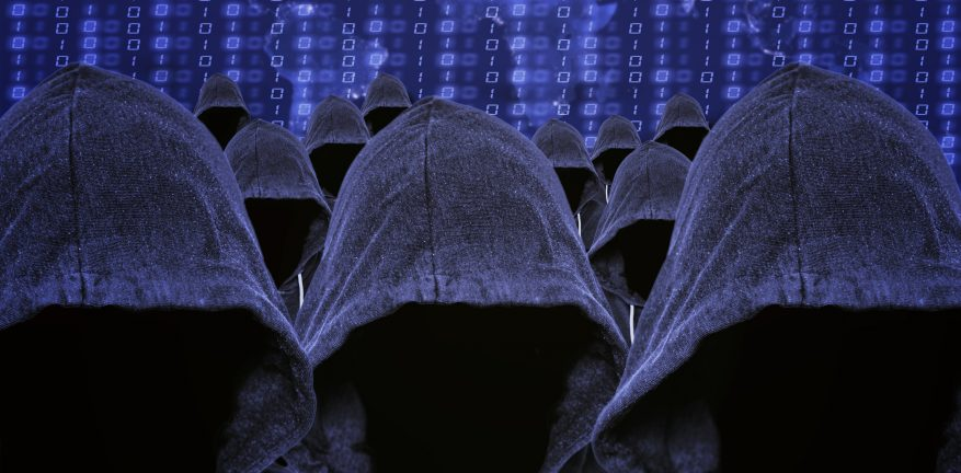 Hooded mass of unknown faceless computer hacker and cyber criminals with a world map of internet usage and binary code