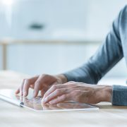 Close-up Shot of a Man Hands Using Transparent Keyboard of High-Tech Computer with Transparent Display In the Near Future. Light Modern Room