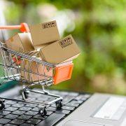 E-commerce symbol of shopping cart over laptop
