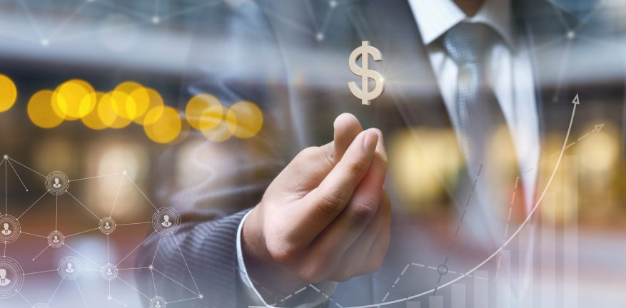 Businessman with dollar sign on blurred background.