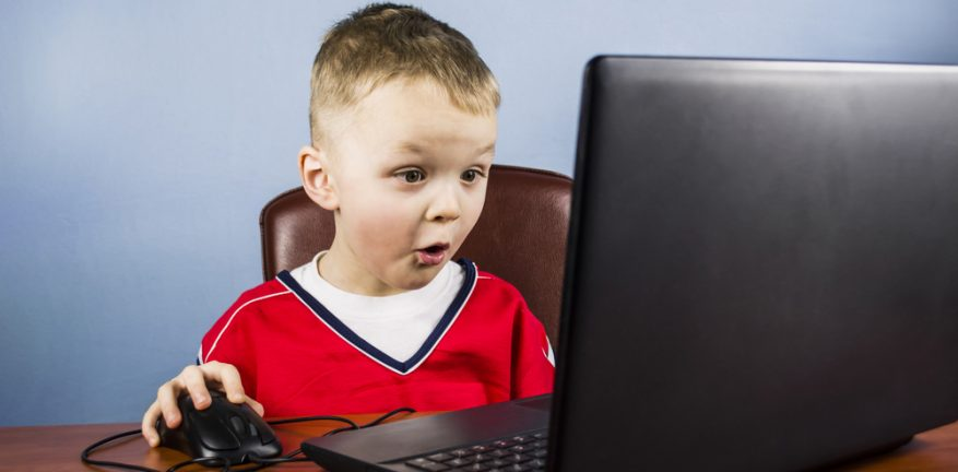 Young boy at desk using laptop