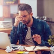 Frustrated young man massaging his nose and keeping eyes closed while sitting at his working place in office