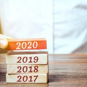 Businessman builds wooden blocks 2020. The concept of the beginning of the new year. New goals. Next decade. Trends and changes in the world. Build plans and planning. Time report