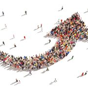Large group of people in the shape of an arrow pointing up symbolizing direction , progress or growth.
