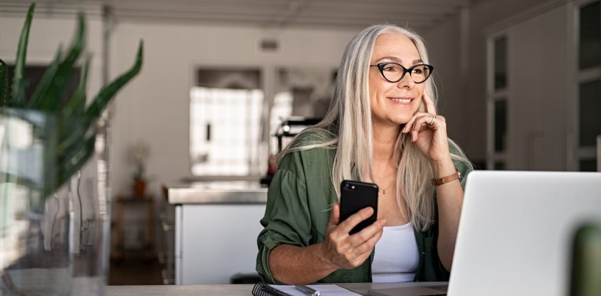 Happy senior woman holding smartphone and laptop daydreaming while looking away. Successful stylish old woman working at home while thinking about a good future. Cheerful fashionable lady entrepreneur wearing cool eyeglasses.