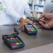 Wireless payment using smartphone and NFC technology. Close up. Male Customer paying with smart phone in pharmacy. Close Up shopping. Modern technology and people concept - Mixed race Woman with payment terminal and male customer with smartphone paying for medications.