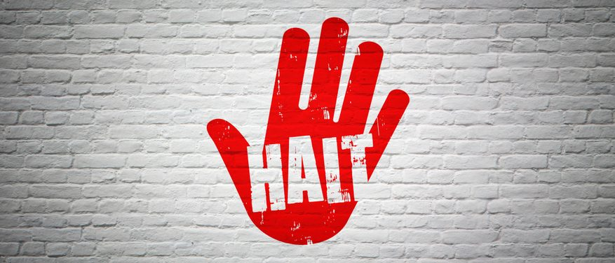 Halt - red hand painted on white wall