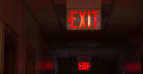 Lit exit signs down hallway