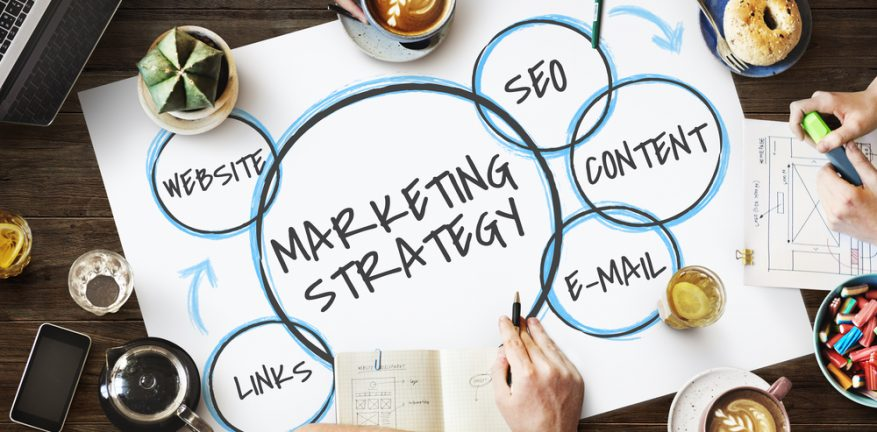 Words marketing strategy on paper surrounded by staff