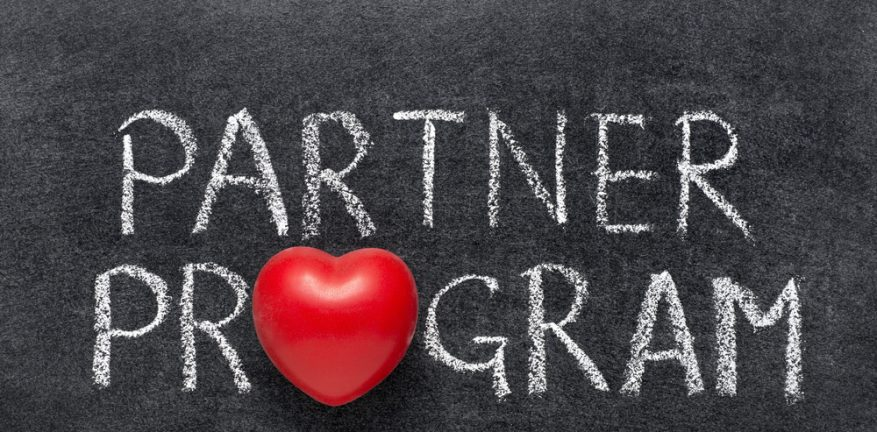 Words partner program with the o in partner a heart, on a blackboard