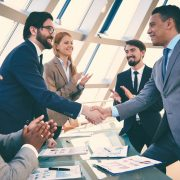 Businesspeople shaking hands at conference room table