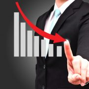 Man pointing to graph showing revenue decline
