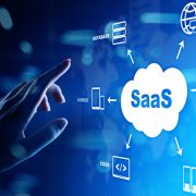 Hand pointing at digital depiction of word SaaS in a cloud