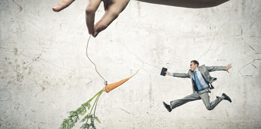Businessman chasing after a dangling carrot incentive