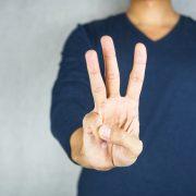 Man holding up three fingers