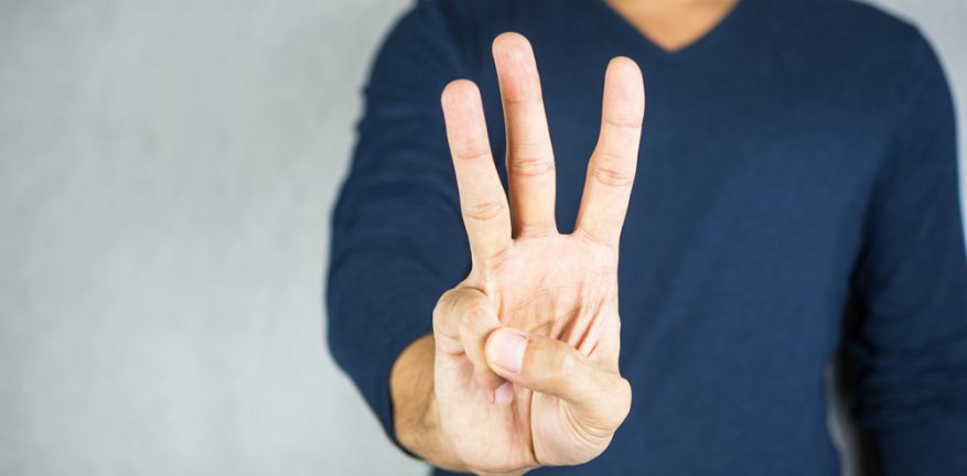 Man holding up three fingers