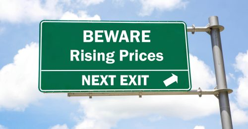 Green,Overhead,Road,Sign,With,A,Beware,Rising,Prices,Next